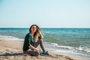 Girl in sportswear fitness by the sea listening