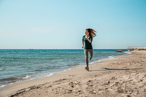 Girl in sportswear running along the sea
