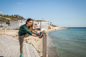Girl in sportswear doing stretching by the sea