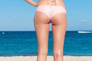 Sexy back of a beautiful woman on tropical beach in small sexy bikini. Bali island.