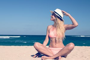 Lonely young sexy woman sitting on the tropical beach by the sea with hat and in the swimsuit. Bali island vacation concept.