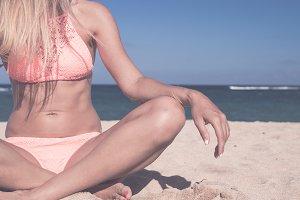 Closeup of woman doing yoga on the beach. Bali island, Indonesia.