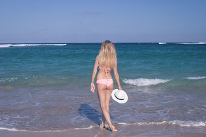 Young blonde woman with hat and in swimsuit is coming into the ocean of tropical Bali island, Indonesia.