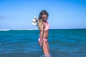 Beautiful young woman in bikini on the beach splashing water. Tropical island Bali, Indonesia.