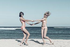 Two happy female friends having fun and swirling on the tropical beach of Bali island, Nusa Dua, Indonesia.