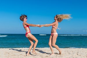 Two happy female friends having fun and swirling on the tropical beach of Bali island, Nusa Dua, Indonesia.