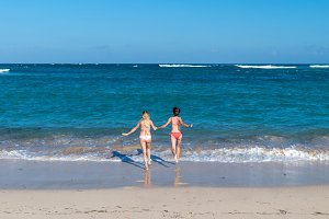 Two sexy beautiful young girls running in the sea. Bali island.