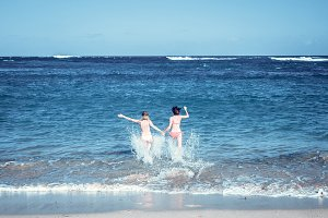 Two sexy beautiful young girls running in the sea. Bali island.