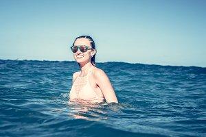 Beautiful young sexy woman enjoying swimming in refreshing sea water. Bali island.
