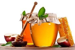 Glass cans full of honey, apples