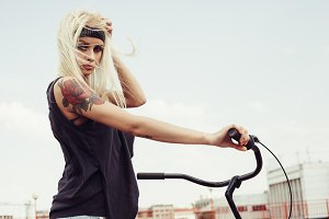 Pretty blonde woman with bike in city