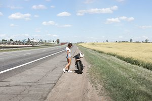 Biker girl stands on the road
