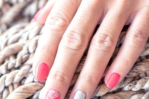 Closeup of hands of a young woman with red manicure on nails against wooden background.