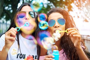 Carefree girlfriends playing with bubble wands outside in summer