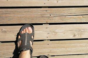 Feet of man walking on a footbridge