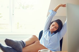 Stretching young woman with feet on desk
