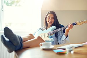 Beautiful girl singing while playing her guitar