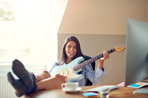 Joyful woman with guitar in front of monitor