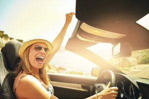 Cheerful woman laughing and sitting in cabriolet