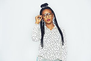Stylish young black woman standing and touching goggles