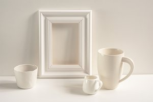 White frame and a set of white cups