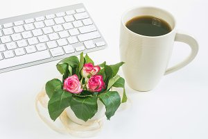Tiny roses and a cup with coffee