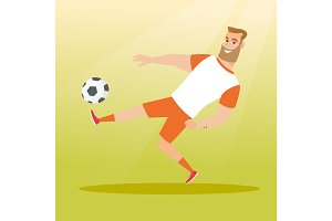 Young caucasian soccer player kicking a ball.
