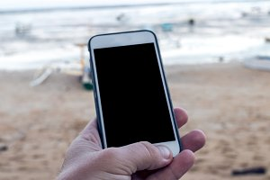Man hand with smartphone with empty space on a beach background, Bali.