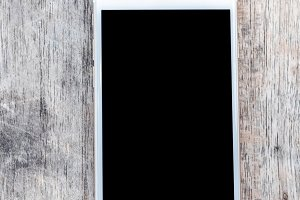 Top view image of smartphone over wooden table room for text, ready for mockup. Empty space.