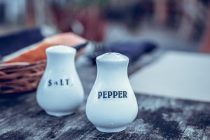 Glass salt and pepper shakers on a wooden table in restaurant, Bali island.