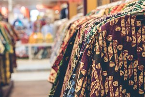 Clothes hang on a shelf in a shopping mall on Bali island, Indonesia. Indonesian cotton batik.