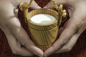 Vintage small wooden mug of milk