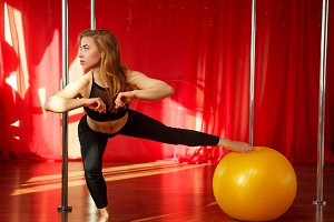 Pole dancer stretches before classes