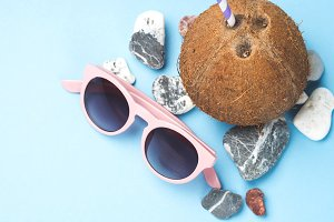 Sun glasses, sea stones and coconut