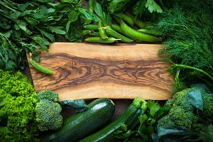 Frame of green vegetables and herbs around cutting board.