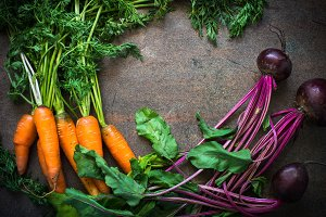 Carrots and beets on dark stone table.