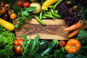 Organic farmer vegetables around cutting board.