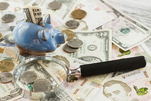 Different coins and banknotes with a magnifying glass and piggy bank