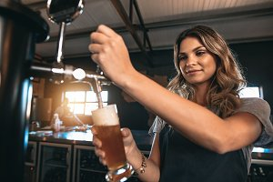 Beautiful female bartender tapping
