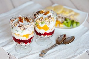 Delicious healthy dessert with cottage cheese, raspberry jam, fruit and muesli on a wooden background