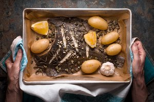 Baking tray with flounder and seasoning in the hands top view