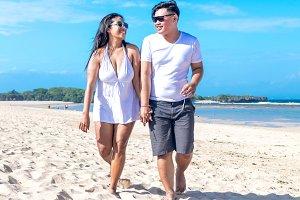 Asian couple walking on the beach of tropical Bali island, Indonesia.