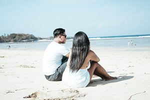 Asian couple sitting on the beach of tropical Bali island, Indonesia.