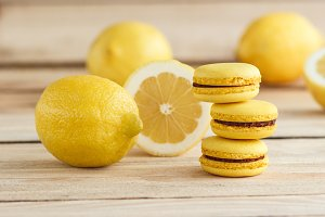 Yellow french macarons with lemons on the wooden board