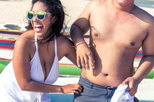 Asian couple having fun on the beach of tropical Bali island, Indonesia.