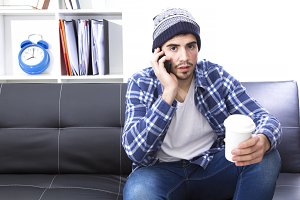 Young man in the office with cellphone and coffee