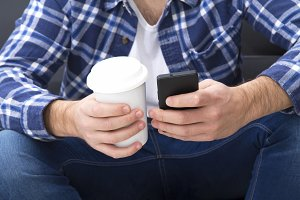 young man with cellphone and coffee