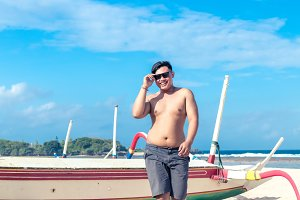 Young asian indonesian man on the beach of tropical Bali island, Indonesia.