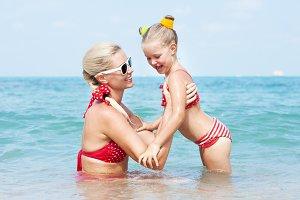 Mother teaching daughter to swim