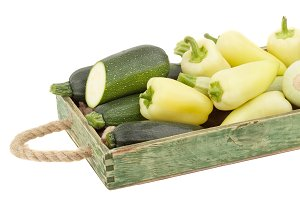 Green fresh bell peppers and zucchini in the wooden tray, isolated